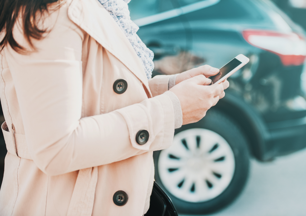 woman buying a car parking ticket on her phone in a car park
